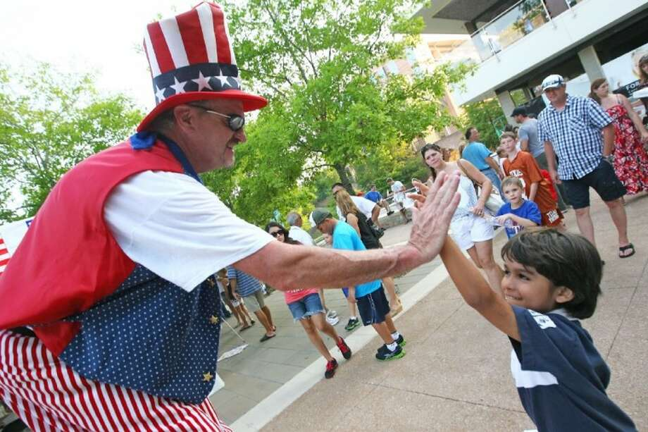 Fireworks will explode over The Woodlands Town Center area on July 4 at 9:15 p.m. The fireworks extravaganza will culminate a day full of Fourth of July events in The Woodlands. Below a youngster gets a high five from a festivalgoer dressed up as Uncle Sam at the Red, Hot and Blue Festival in The Woodlands. This year's event takes place from 6-10 p.m. in The Woodlands. Photo: Staff Photo By Karl Anderson