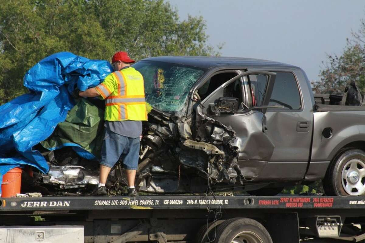 A wrecker driver covers the front of a Ford F-150 following a head on collision on Interstate 45. The truck was driven by Nicole Baukus of Spring and was headed the wrong way on the highway when she collided with a Chevrolet Aveo.
