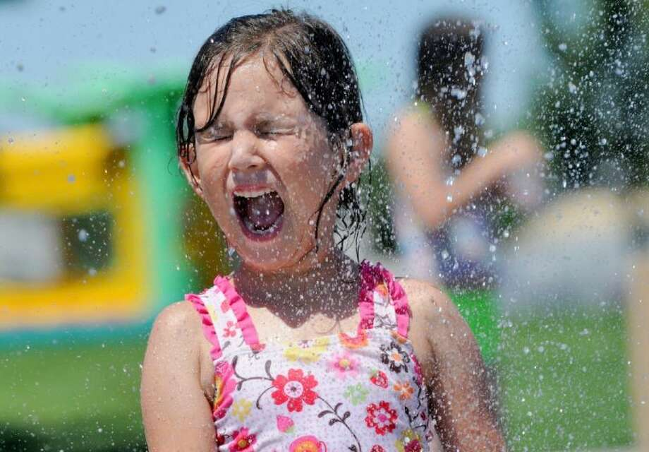 Kayla Holdridge, 6, of Eagle, is sprayed with water at Settlers Park in Meridian, Idaho. Many people looked for ways to beat the heat as temperatures in the Treasure Valley soared into the triple digits. Photo: Adam Eschbach