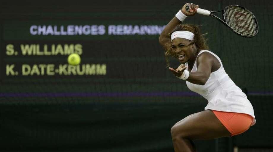 Serena Williams plays a return to Kimiko Date-Krumm during their Wimbledon match. Williams won in straight sets. Photo: Anja Niedringhaus