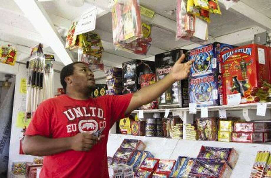 Antuan Rofe talks about the firework allowed this year at the Texas Outlaw fireworks stand on East FM 242 near I-45 Tuesday. Fireworks stands around the area opened for business Monday and will close July 6. Photo: Staff Photo By Jason Fochtman / Conroe Courier