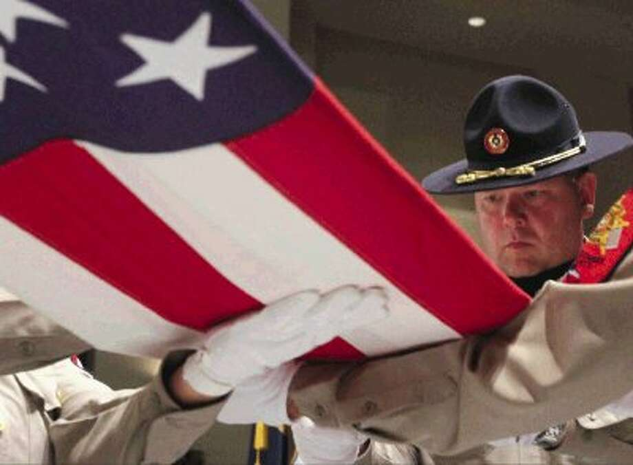 "Members of the Montgomery County Sheriff's Honor Guard fold a flag during Mims Baptist Church's ""Celebrate America' service Sunday. The service featured Senator Dan Patrick as a guest speaker and a variety of patriotic activities honoring troops. Go to HCNPics.com to view and purchase this photo, and others like it. Photo: Staff Photo By Jason Fochtman / Conroe Courier"