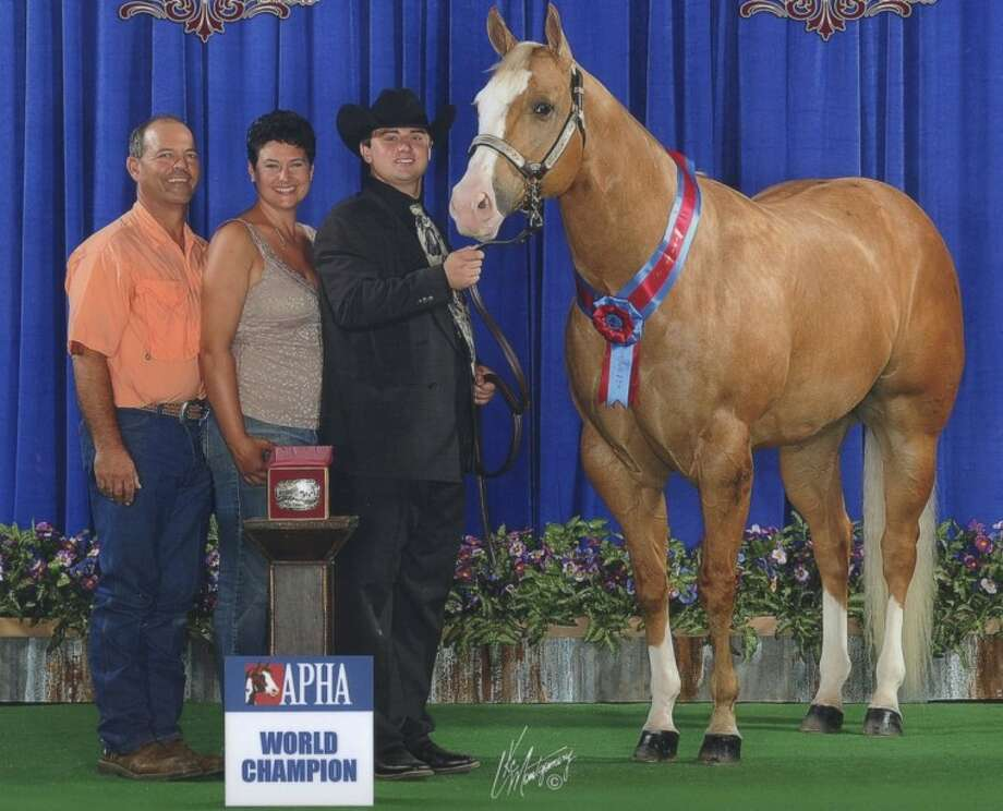 Hunter Griffin, 16, of Conroe, stands with his award-winning show horse Simon after winning the World Champion title in the Aged Geldings division of the American Paint Horse Association's Youth World Show held recently in Fort Worth.