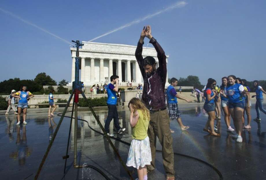 Visitors get much needed relief from a water sprinkler set up at the National Mall near the Lincoln Memorial, rear, in Washington Saturday. Photo: Manuel Balce Ceneta