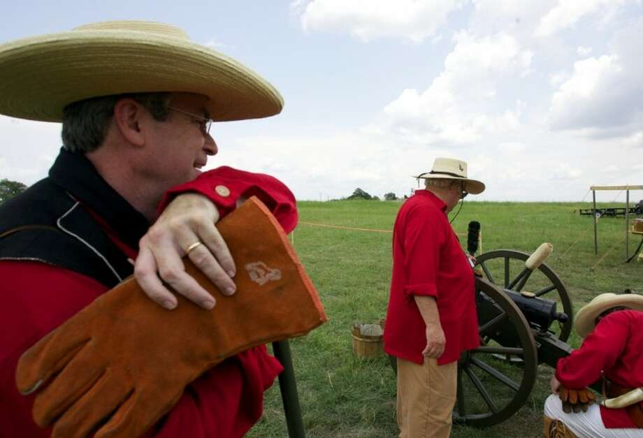 Kameron Searle, descendant of the founder of Montgomery W.W. Shepperd, looks on as fellow members of the Lone Star Volunteers load a replica 1841 Mississippi cannon during Saturday's Montgomery Founder's Day celebration at Fernland Historical Park. Photo: Staff Photo By Eric Swist