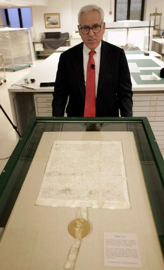 In this March 3, 2008 file photo, David Rubenstein poses with a 1297 Magna Carta document, at the National Archives in Washington. Photo: Susan Walsh