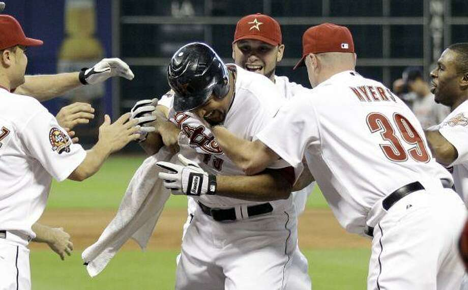 The Astros' Carlos Lee is congratulated by teammates after hitting the game-winning two-run home run against the Washington Nationals in the ninth inning Thursday afternoon at Minute Maid Park. / AP2010