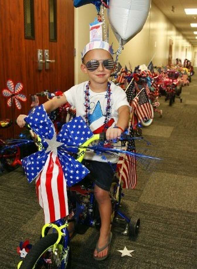 Teacher and Parade Coordinator Cyndi Walker's son, Brandon Walker, 6, rides in last year's Patriotic Parade at The Depot Childcare Center in Conroe.