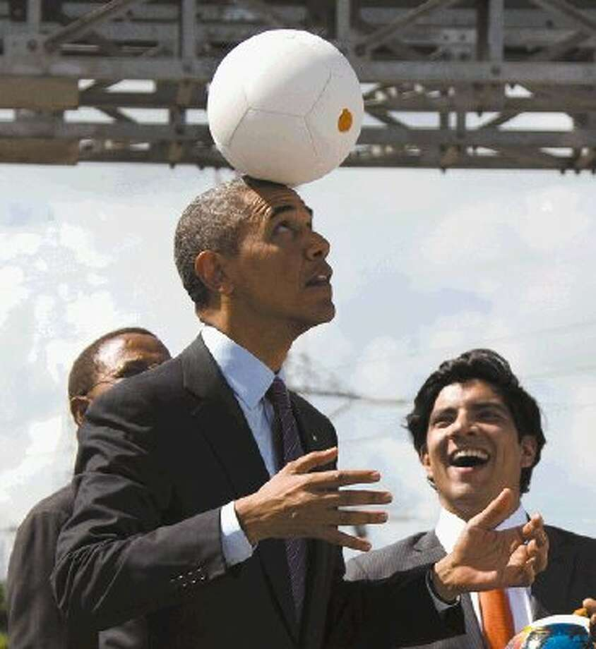 """U.S. President Barack Obama demonstrates """"the Soccket Ball,"""" which uses kinetic energy to provide power to charge a cell phone or power a light, during an event at the Ubungo power plant to promote energy innovation on Tuesday, July 2, 2013, in Dar Es Salaam, Tanzania. The president is traveling in Tanzania on the final leg of his three-country tour in Africa. Photo: Evan Vucci / THE ASSOCIATED PRESS2013"""