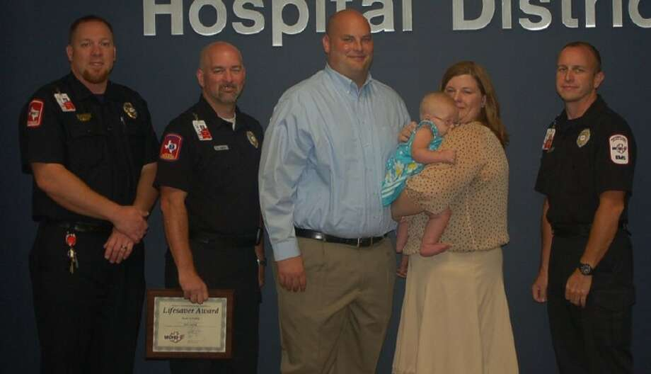 Montgomery County Hospital District staff, left to right, Kevin Nutt, Sean Conley and Steven Lindsay (far right) reunite with cardiac save patient Bailey Fanning and her parents, Jason and Jessica.
