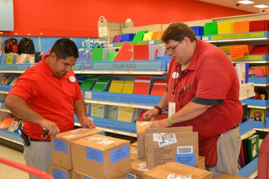 Conroe Target employees Daniel McKee and Will Rankins work Tuesday to unpack boxes of school supplies.