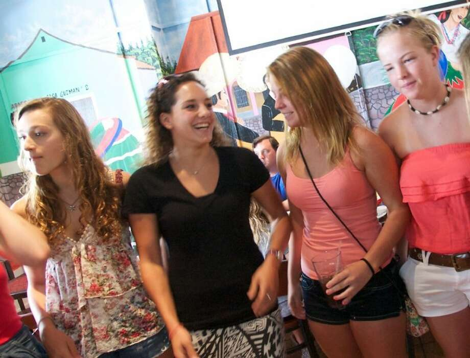 Diver Christina Loukas (black shirt), who qualified for the Olympic Team on the 3M springboard for the second time, chats with friends during a send off and year end celebration for The Woodlands Diving team at Rico's restaurant in The Woodlands.