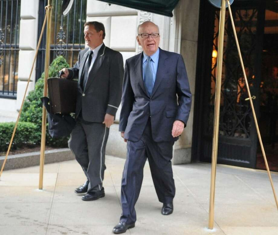 News Corporation head Rupert Murdoch exits his Fifth Avenue residence Thursday in New York. As the scandal runs its course in the U.K., Murdoch's News Corp. must confront at least two U.S.-based shareholder lawsuits, a possible Standard & Poor's credit downgrade, and the beginnings of a federal investigation. Photo: Louis Lanzano