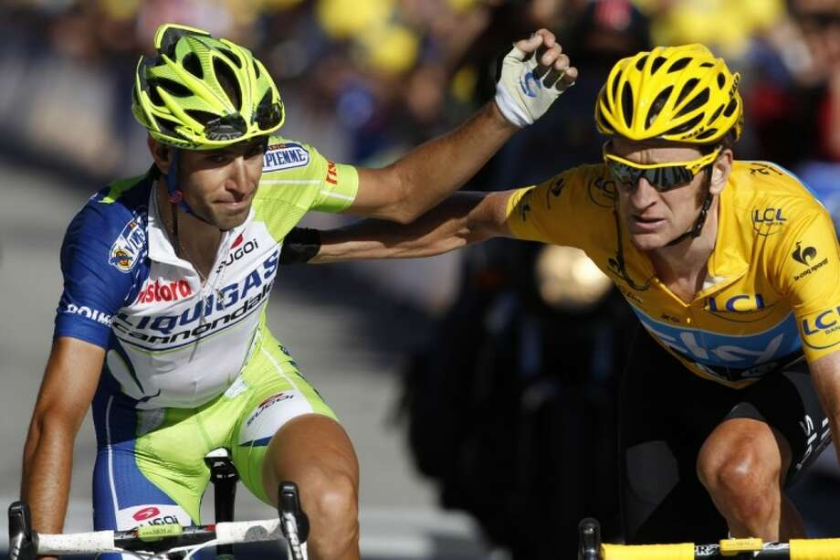 Vicenzo Nibali of Italy, left, and Bradley Wiggins of Britain, wearing the overall leader's yellow jersey, cross the finish line of the 11th stage of the Tour de France in La Toussuire, France, on Thursday. Photo: Laurent Rebours