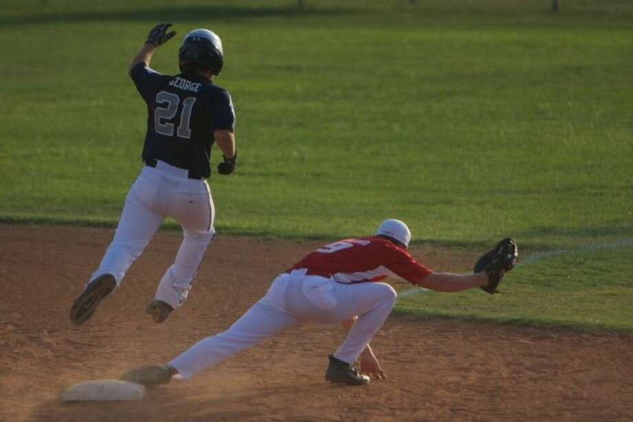 ORWALL National's Cailen George leaps to first base as Bridge City's Andrew Hoyland reaches out for the ball during Thursday night's playoff game at the ORWALL fields in Spring. To view or order this photo and others like it, visit HCNPics.com. Photo: Staff Photo By Eric Swist