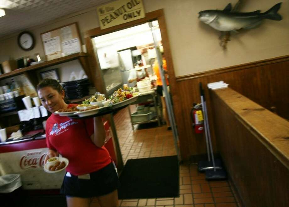 A waitress makes her way out of the kitchen with a plate of fresh food for a table at Vernon's Kuntry Katfish Friday.