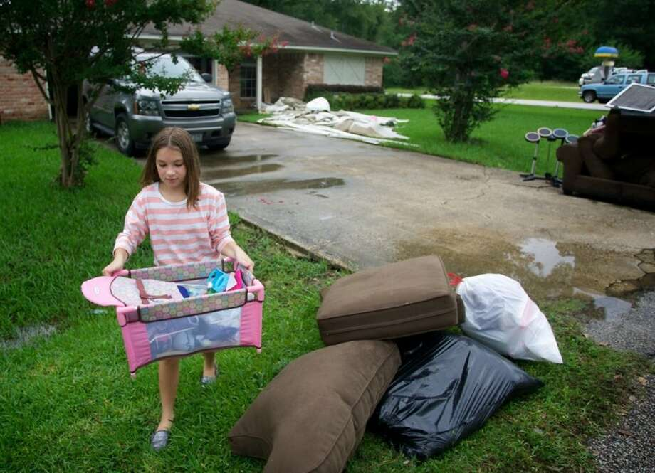 Macey Miller, 10, takes a basket of toys damaged by water to the curb Friday morning at her family's home in the Timber Lakes-Timber Ridge subdivision. Miller's home was flooded by high waters during Thursday's storms. Photo: Staff Photo By Eric Swist