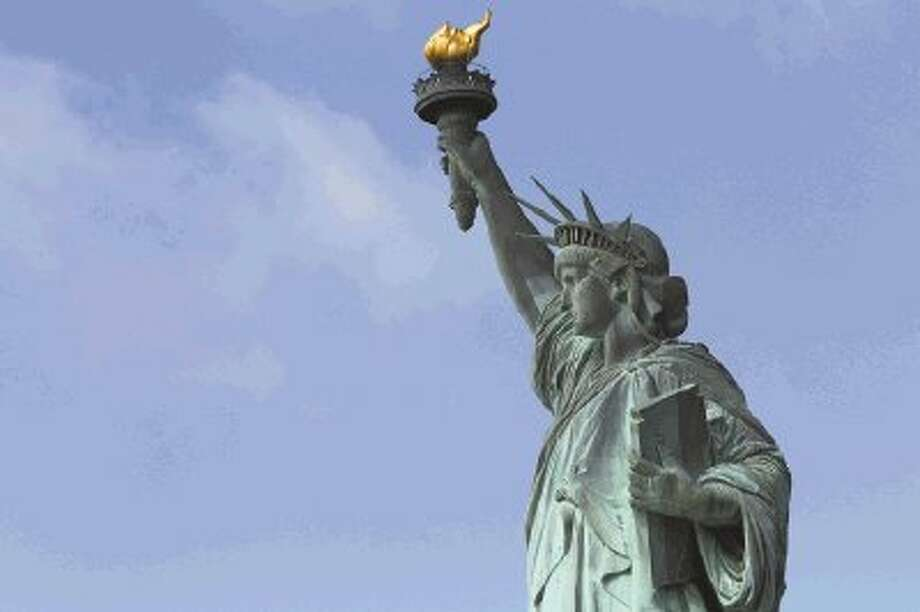 The Statue of Liberty stands against a clear sky Thursday on the first day it opened to tourists since Superstorm Sandy swamped its little island in New York Harbor. Photo: Mary Altaffer / AP2013