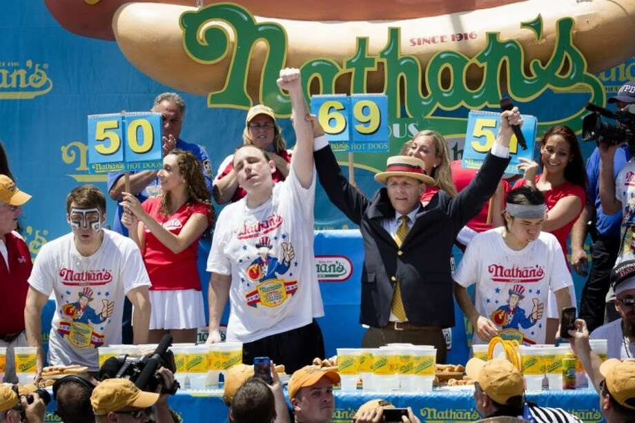 Joey Chestnut won the Nathan's Famous Fourth of July International Hot Dog Eating Contest with a total of 69 wieners and buns on Thursday at Coney Island in the Brooklyn borough of New York. Also pictured are Tim Janus, left, and Matt Stonie. Photo: John Minchillo