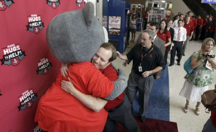 Houston Rockets employees line up to hug Clutch, left, the Houston Rockets mascot, during the launch of the 10,000 Hugs-to-Help fundraising campaign Wednesday in Houston, to assist three surviving children whose parents were killed in a car accident. Photo: David J. Phillip