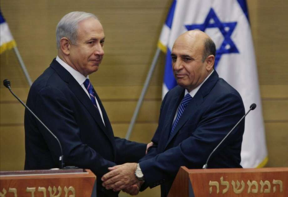 In this May 8, 2012 file photo, Prime Minister Benjamin Netanyahu, left, and Kadima party leader Shaul Mofaz shake hands before holding a joint press conference announcing the new coalition government in Jerusalem. A fierce debate over how to draft religious men into the Israeli military has sparked the first crisis in Netanyahu's newly expanded coalition government. Photo: Sebastian Scheiner