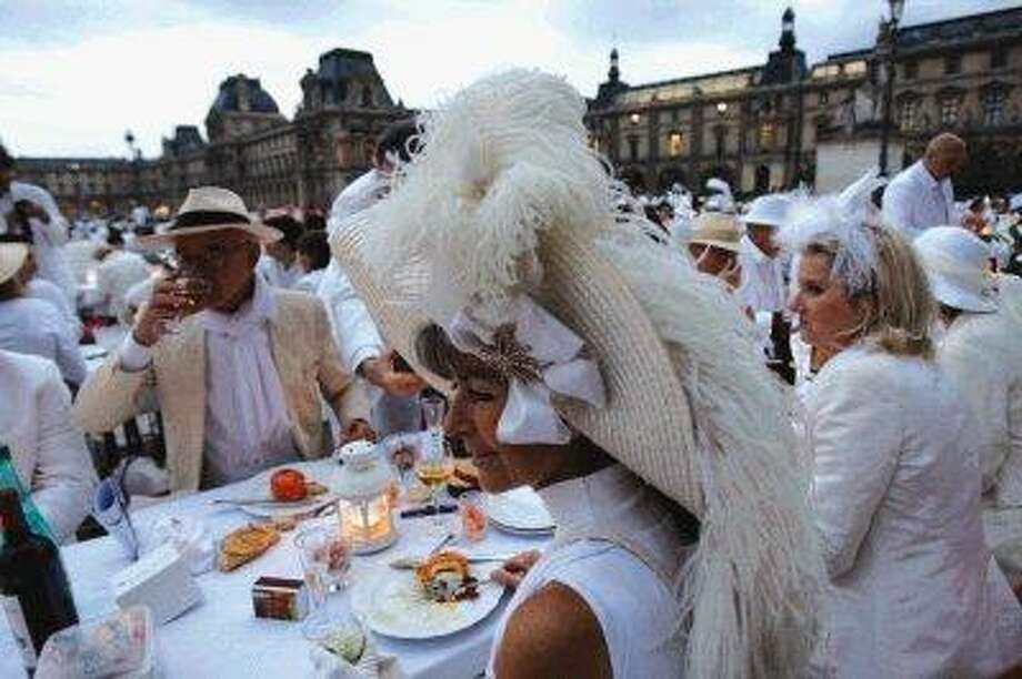 Participants dressed in white take part in a big open air white dinner at the Louvre museum courtyard in Paris, late Thursday. The event is a reminiscent of flash mobs, where hundreds of people descend on one area at a specific time, summoned by SMS text message, gsm phone call or email. / AP