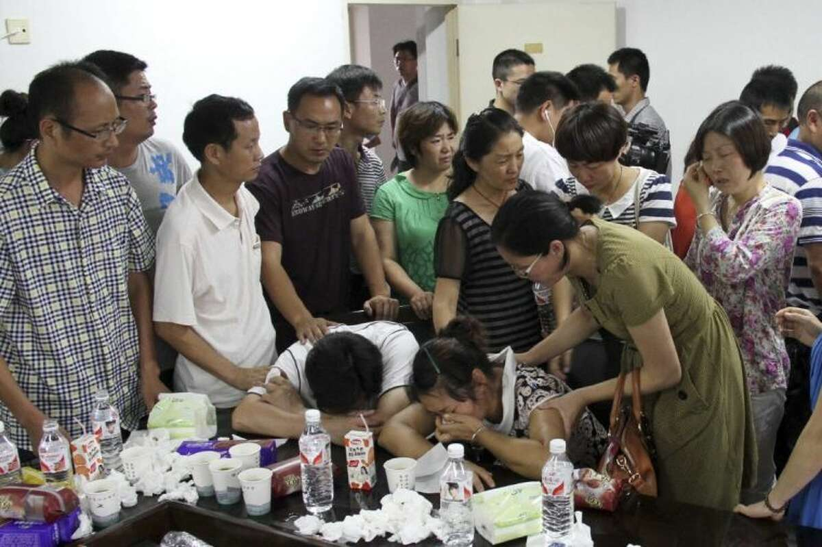Parents of Wang Linjia, center, are comforted by parents of some other students who were on the Asiana Airlines Flight 214 that crashed at San Francisco International Airport, at Jiangshan Middle School in Jiangshan city, in eastern China's Zhejiang province, Sunday.