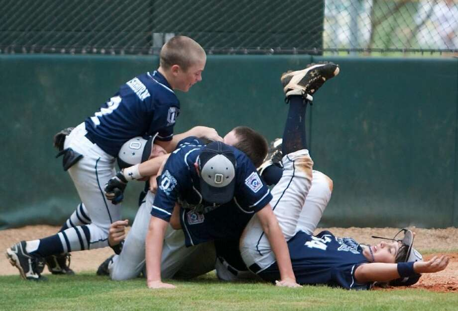A group of players pile atop each other on home plate after ORWALL National defeated Bridge City to claim the Little League Texas East Section 2 championships. Photo: Staff Photo By Eric Swist