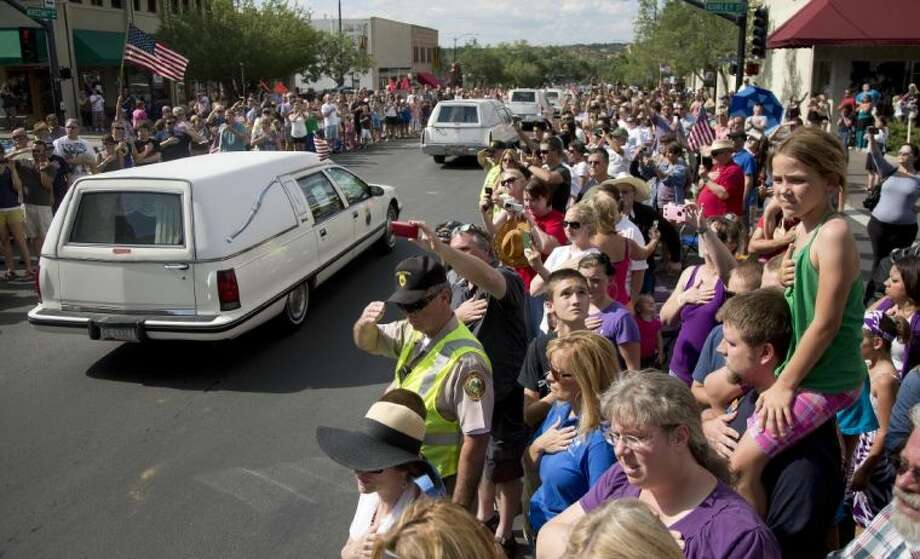 Hundreds of people line Montezuma Street Sunday, July 7, 2013 in downtown Prescott, Ariz. to pay respects as 19 hearses slowly roll by carrying the 19 Granite Mountain Hotshot firefighters killed a week ago by an out-of-control blaze near Yarnell, Ariz. The nearly five-hour-long procession began near the state Capitol in Phoenix, went through the town where the Granite Mountain Hotshots were killed and ended in the mountain community of Prescott, where they lived and will be laid to rest this week. Photo: Julie Jacobson
