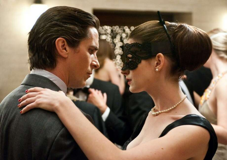 """Christian Bale as Bruce Wayne, left, and Anne Hathaway as Selina Kyle in a scene from the action thriller """"The Dark Knight Rises."""""""