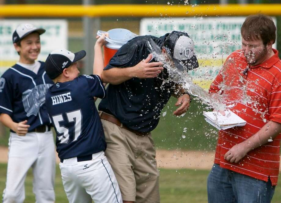 Hunter Hines douses his father, ORWALL National manager Bryan Hines, with water after ORWALL National defeated Bridge City on Saturday to win the Little League Texas East Section 2 championship. Photo: Staff Photo By Eric Swist