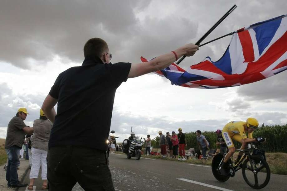 A supporter waves the British flag as Bradley Wiggins of Britain, wearing the overall leader's yellow jersey, passes on his way to winning the 19th stage of the Tour de France on Saturday. The stage was an individual time trial over 33.2 miles with the start in Bonneval and finish in Chartres, France. Photo: Christophe Ena