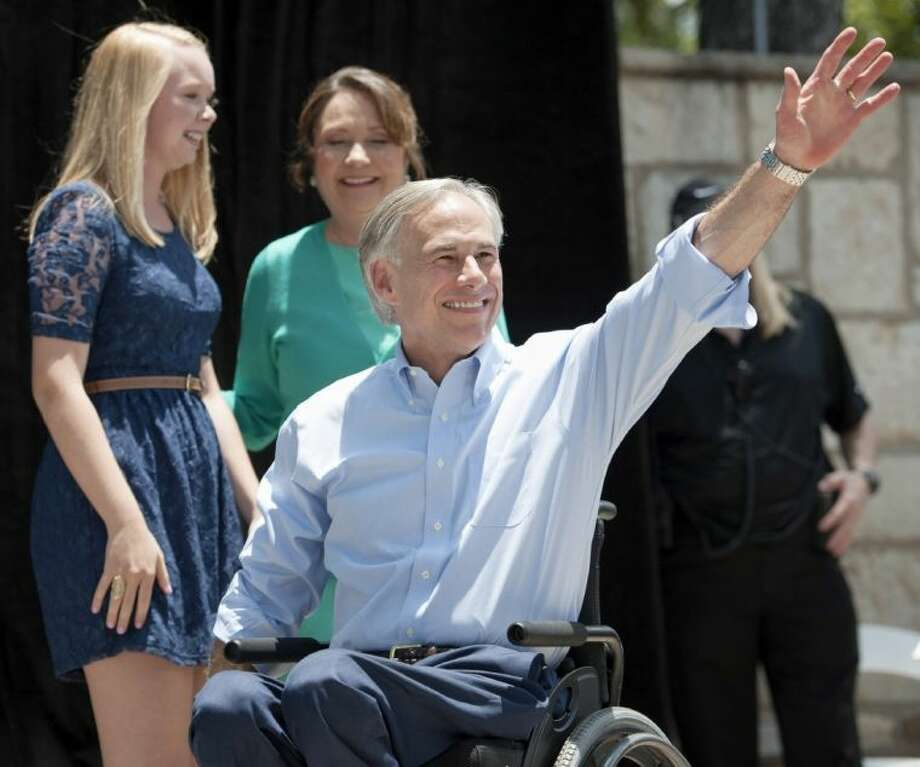 Texas Attorney General Greg Abbott waves to supporters as he takes the stage during an event to announce his 2014 campaign for governor Sunday in San Antonio. Photo: Darren Abate