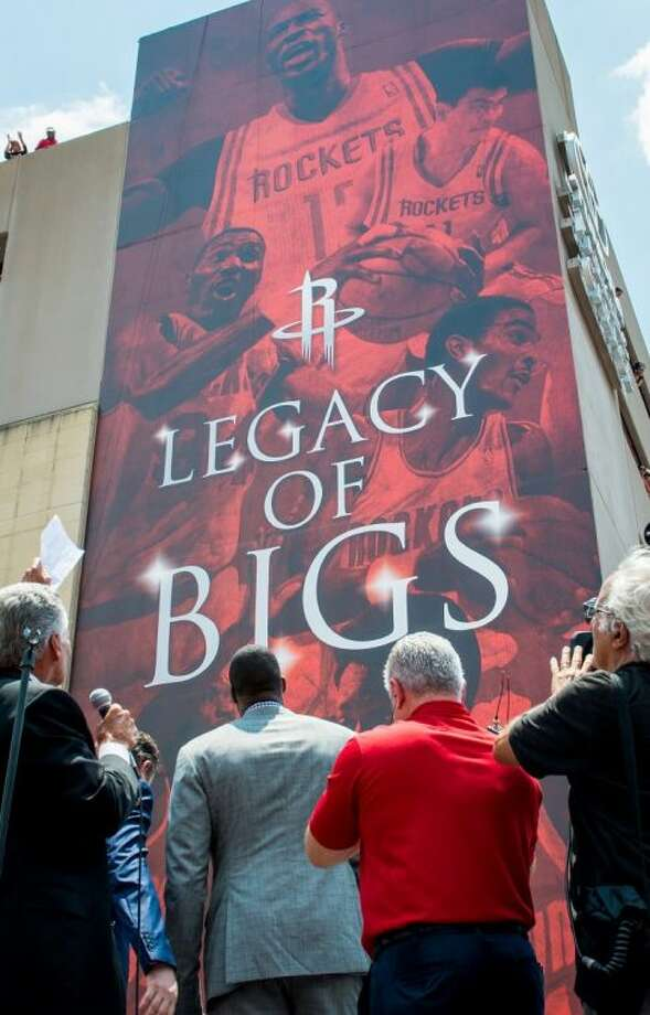 Houston Rockets announcer Bill Worrell, left, gestures to a large banner featuring franchise legends as Dwight Howard, center, is introduced as the newest member of the team during a ceremony at the Toyota Center on Saturday in Houston. Photo: Smiley N. Pool