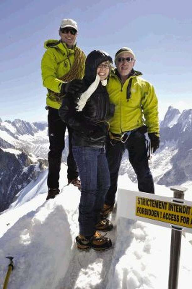 Former U.S. congresswoman Gabrielle Giffords, center, who is recovering from injuries in a mass shooting last year, and her astronaut husband Mark Kelly, right, accompanied by mountain guide Vincent Lameyre, left, stand on a ridge of the Aiguille du Midi, above Chamonix, France in the French Alps on Monday after riding a cable car up and walking a few meters onto the snow, away from a viewing post. The outing was part of her first trip abroad since being shot in the head in a mass shooting in the U.S. last year. Photo: Uncredited / AP2012