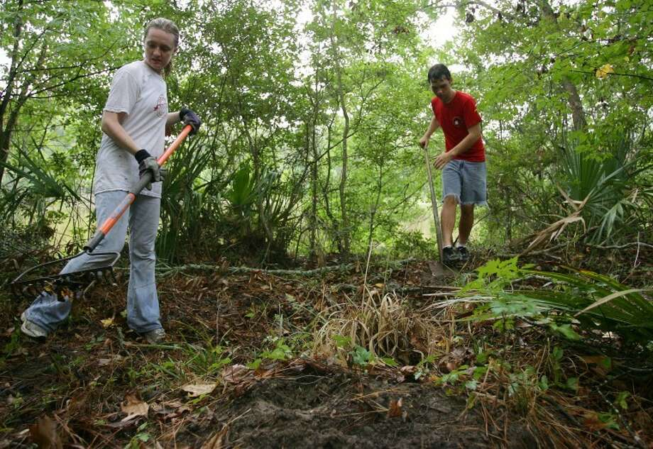 Volunteers Stephanie Reed and Michael Hammon work to clear a walking trail Saturday at the Mussel Pond Preserve in Conroe. Volunteers and members of the Bayou Land Conservancy spent Saturday morning clearing walking trails throughout the preserve.