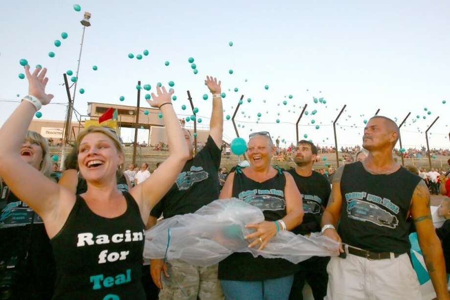 Ruth Helton, center, who is battling ovarian cancer, watches as 650 teal balloons are released by fans and supporters Saturday at Gator Motorplex in Willis. Photo: Staff Photo By Karl Anderson