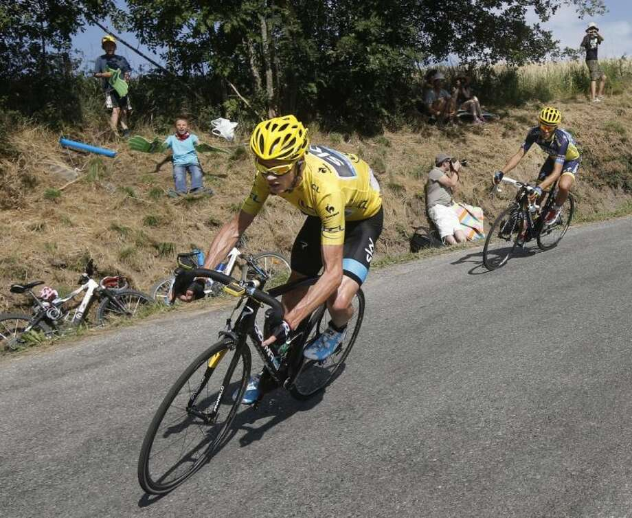 Christopher Froome of Britain, wearing the overall leader's yellow jersey, and Spain's Alberto Contador speed down the Col de Manse in the last kilometers of the sixteenth stage of the Tour de France on Tuesday. Photo: Laurent Cipriani