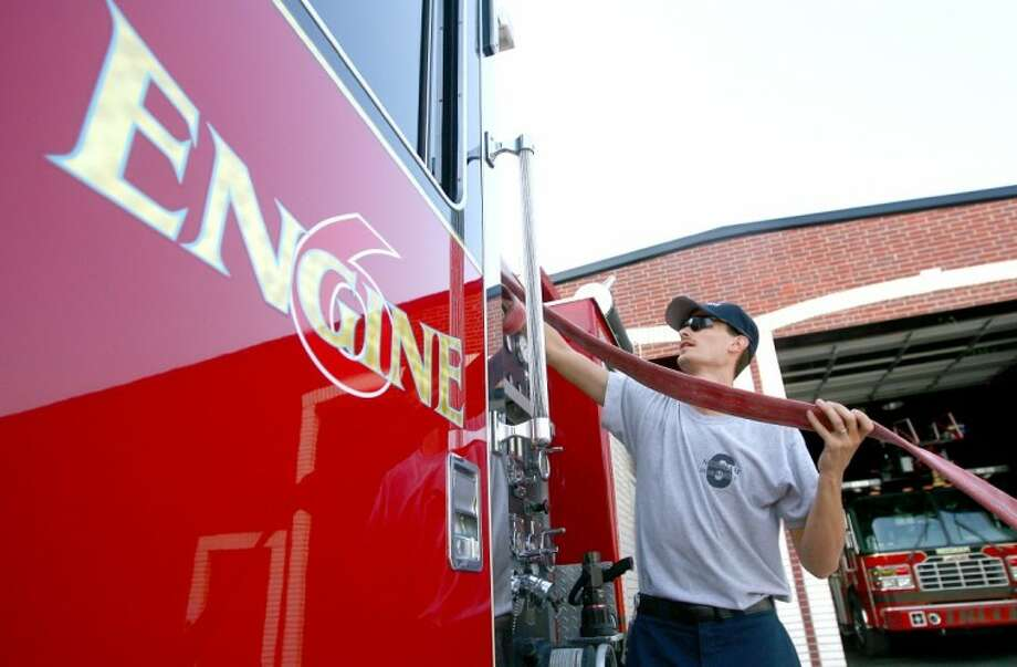 Cody Tweedy loads a hose into an engine at the Needham Fire Department. Photo: Staff Photo By Karl Anderson