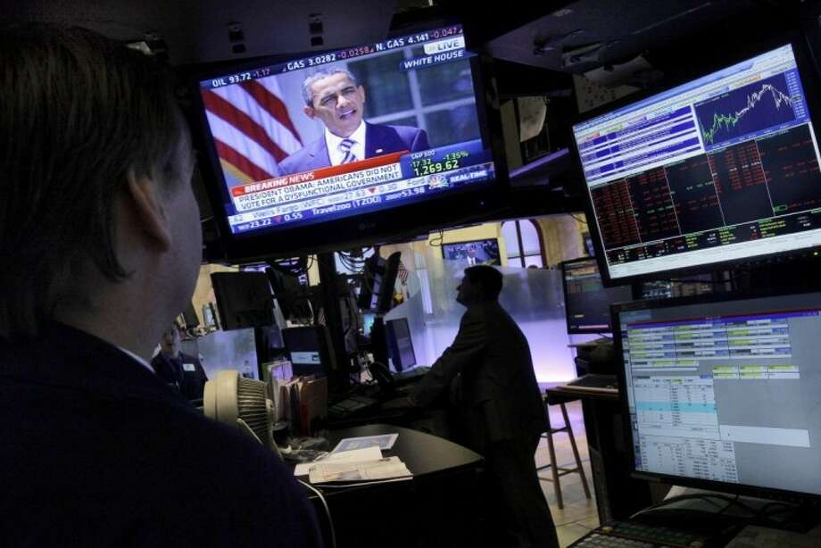Specialists watch President Barack Obama on television monitors on the floor of the New York Stock Exchange Tuesday. The stock market stumbled again Tuesday and is on pace for its longest losing streak in two years. See story, page 7A. Photo: Richard Drew