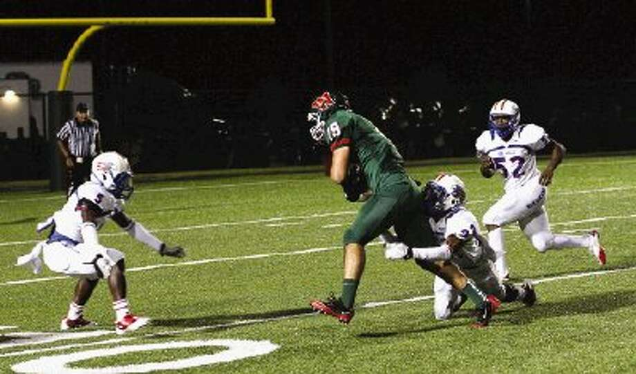 The Woodlands' Jayme Taylor fights for additional yardage in a game against Oak Ridge last season.