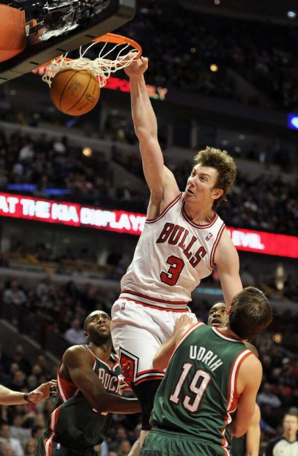 The Chicago Bulls' Omer Asik dunks the ball over Milwaukee Bucks' Beno Udrih during the second half of a Feb. 22 game in Chicago. Photo: Jim Prisching