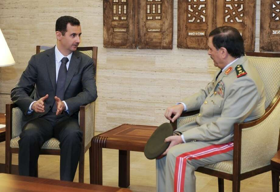 In this file photo released by the Syrian official news agency SANA on July 19, Syrian President Bashar Assad, left, meets with Fahd Jassem al-Freij, Syria's new Defense Minister, in Damascus, Syria. Photo: HOPD