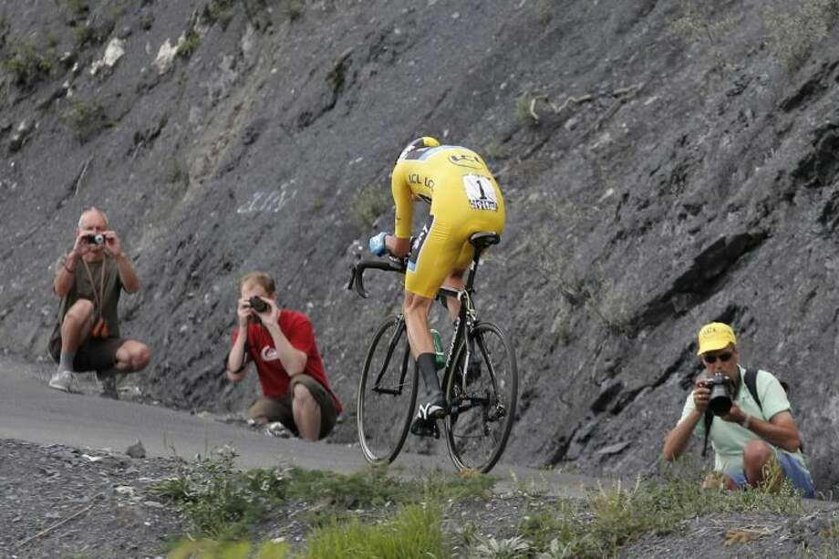 Spectators take pictures as stage winner Christopher Froome of Britain, wearing the overall leader's yellow jersey, passes during Wednesday's 17th stage of the Tour de France over 20 miles with a start in Embrun and finish in Chorges, France. Photo: Christophe Ena