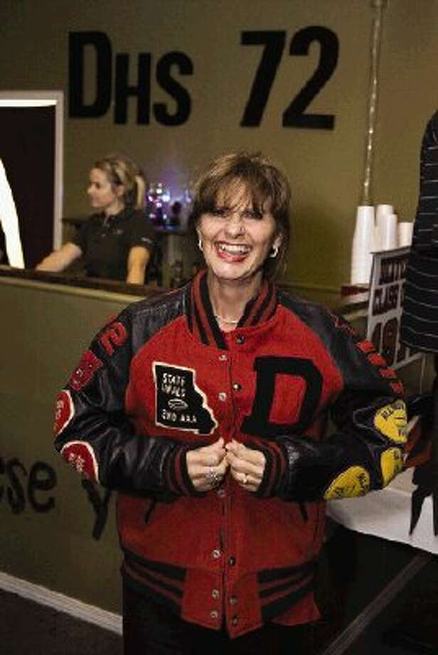 Nancy Meyer puts on an old letterman's jacket at the Dexter High School class of 72 reunion.