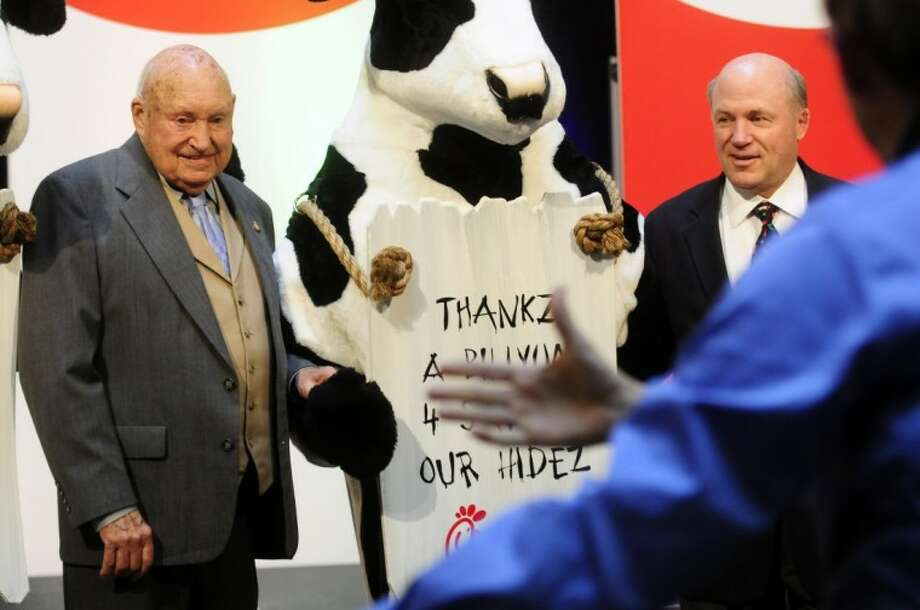In this Dec. 14, 2009 photo, Chick-fil-a founder Truett Cathy, left, and his son Dan Cathy pose for a photo with the Chick-fil-A cows during a celebration of passing the $3 billion mark in system-wide sales for the first time at the Chick-fil-a headquarters in Atlanta. Chick-fil-A, whose founder distinguished the fast-food chain by closing on Sunday out of religious piety, continues to mix theology with business and finds itself on the front lines of the nation's culture wars after its president, Dan Cathy, confirmed his opposition to gay marriage in June 2012. Photo: Elissa Eubanks