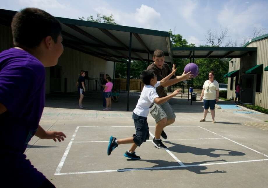 Camp counselor Steven Matthews plays a game of basketball with campers at the Oscar Johnson Jr. Community Center in Conroe. Camp Fun Quest is tracking students' activity levels and converting them into miles for the Million Miles Challenge. Photo: Staff Photo By Eric Swist