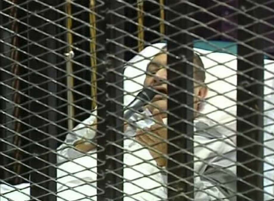 This video image taken from Egyptian State Television shows 83-year-old former Egyptian president Hosni Mubarak speaking to the court, using a microphone while laying on a hospital bed inside a cage of mesh and iron bars in a Cairo courtroom Wednesday.