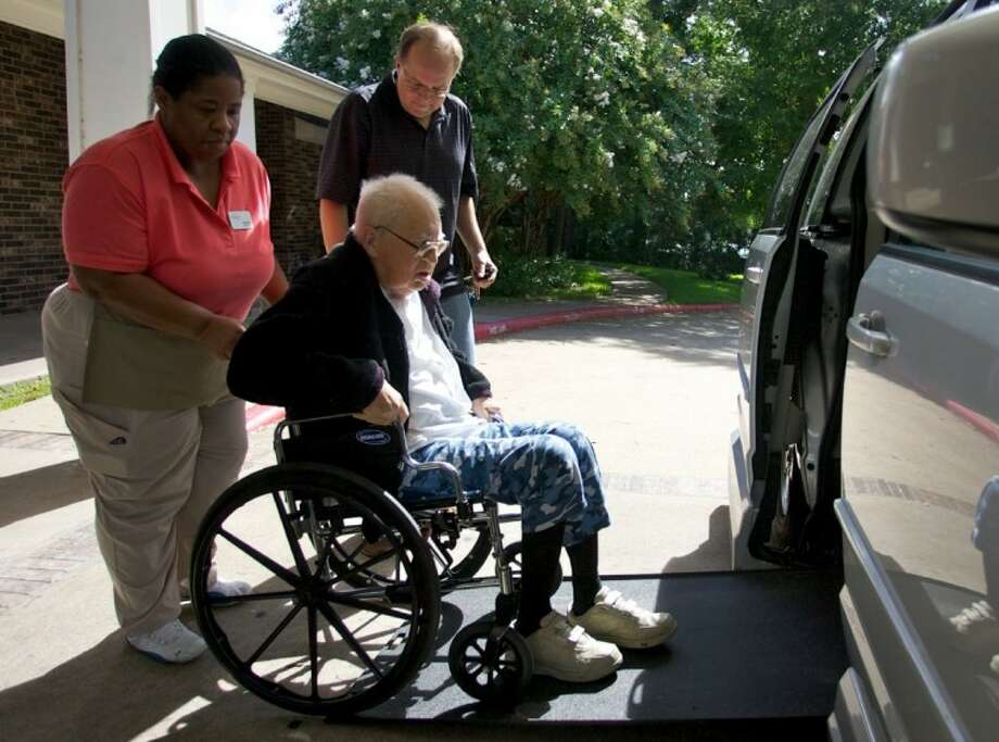 Ihor Koszman is helped into a van by nurse Damita Hatchett as his son Victor looks on. Elmcroft of Rivershire assisted-living center in Conroe partnered with nonprofit Second Wind Dreams to send Koszman to Martin Creek State Park in Henderson. Koszman wanted to spend time with his wife and son back in nature. Photo: Staff Photo By Eric Swist
