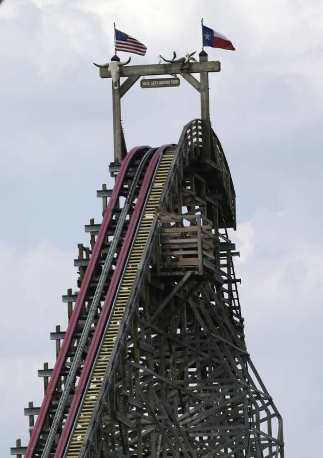 The Texas Giant roller coaster ride sits idle at the Six Flags Over Texas park Saturday, July 20, 2013, in Arlington, Texas. Investigators will try to determine if a woman who died while riding the roller coaster at the amusement park Friday night fell from the ride after some witnesses said she wasn't properly secured. Photo: LM Otero